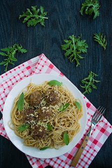 Pasta with meatballs and parsley in tomato sauce