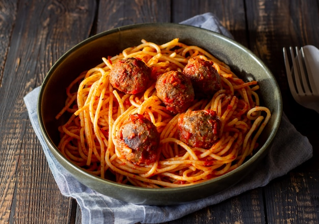 Pasta with meatballs and tomato sauce on a wooden background.