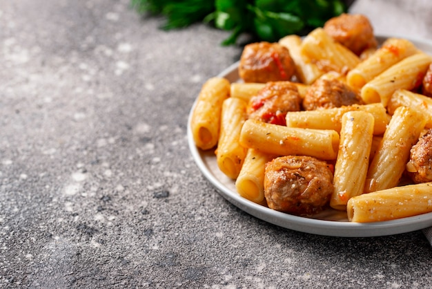 Pasta with meatballs in tomato sauce.