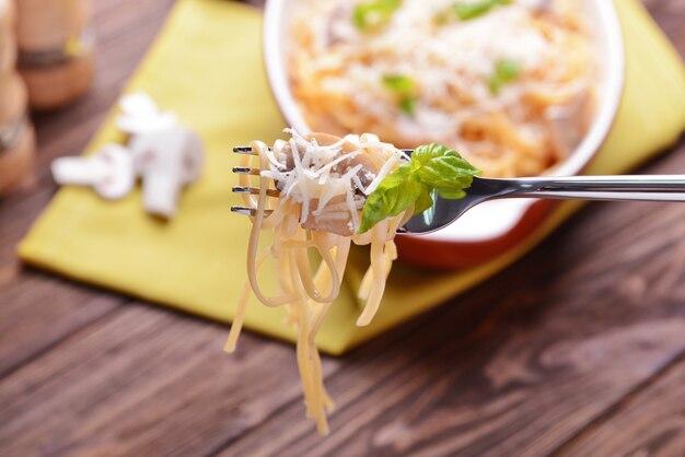 Паста с грибным соусом насаженная на вилку, крупным планом