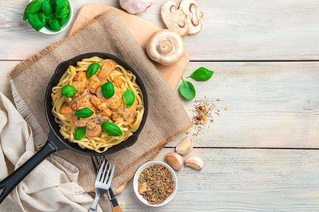 Паста с грибами со сливочно-томатным соусом на столе из пряностей из грибов и базилика.