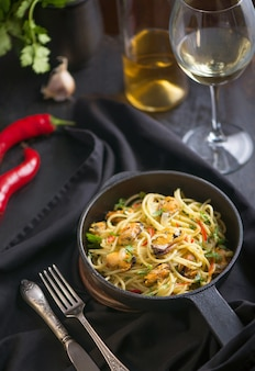 Pasta with mussels, a glass of white wine dark background