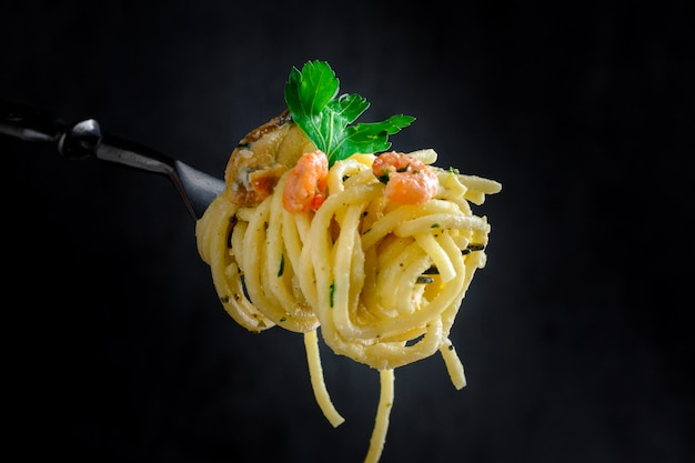Pasta with mussels and prawns on a fork on a dark background