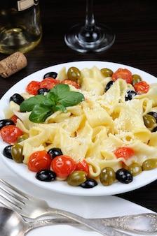 オリーブ、ニンニク、バジル、トマトのパスタにパルメザンチーズで味付け。