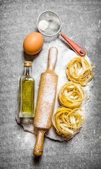 石のスタンドにオリーブオイル、ふるい、めん棒、小麦粉のパスタ。石のテーブルの上。上面図