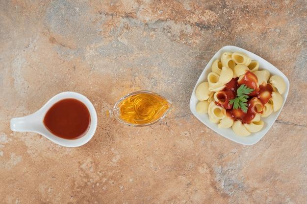 油とオレンジ色の背景にパセリとソースのパスタ