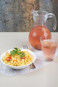 白いボウルとレモネードにパセリとトマトのスライスが入ったパスタ