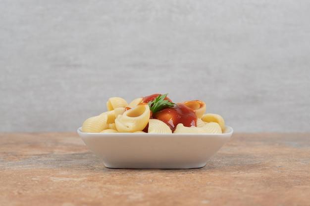 Pasta con prezzemolo e salsa su spazio arancione.