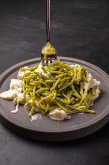 Паста с соусом песто и стракателлой, подается на серой керамической тарелке и вилке на темном текстурированном фоне, вертикальный вид, выборочный фокус