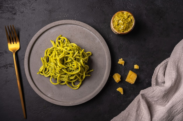 Pasta with pesto and parmesan, served on gray ceramic plate and golden fork on dark textured backgroun, top view