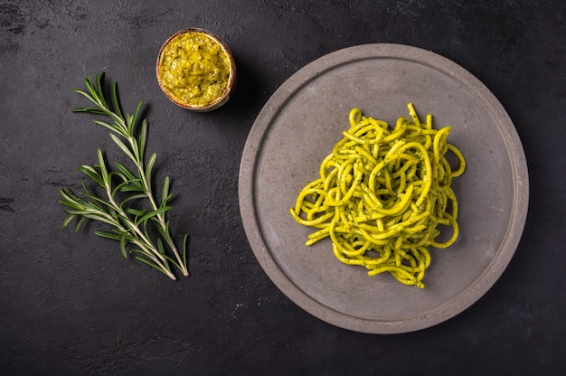 Pasta with pesto and rosemary, served on gray ceramic plate on dark textured background, selective focus, top view, copy space