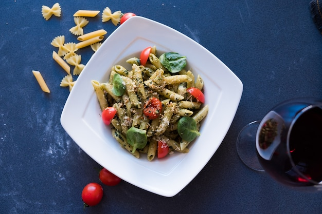 Pasta with pesto sauce, fresh basil and nuts on white plate on dark blue background
