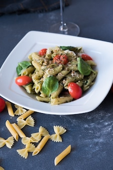 Pasta with pesto sauce, fresh basil and nuts on white plate. spaghetti on dark blue background