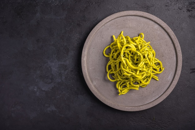 Pasta with pesto, served on gray ceramic plate on dark textured background, selective focus, top view, copy space