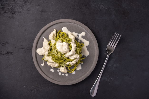 Pasta with pesto and stracatella, served on gray ceramic plate and fork on dark textured backgroun, top view