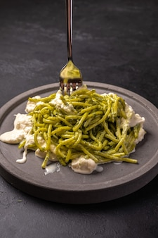 Pasta with pesto and stracatella, served on gray ceramic plate and fork on dark textured backgroun, vertical view, selective focus