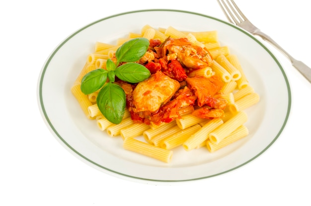 Pasta with pieces of chicken, tomatoes and sweet paprika.