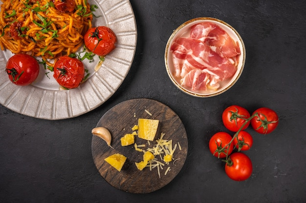 Pasta with prosciutto ham, cherry tomatoes, parmesan and pesto sauce on dark graphite background, top view, copy space
