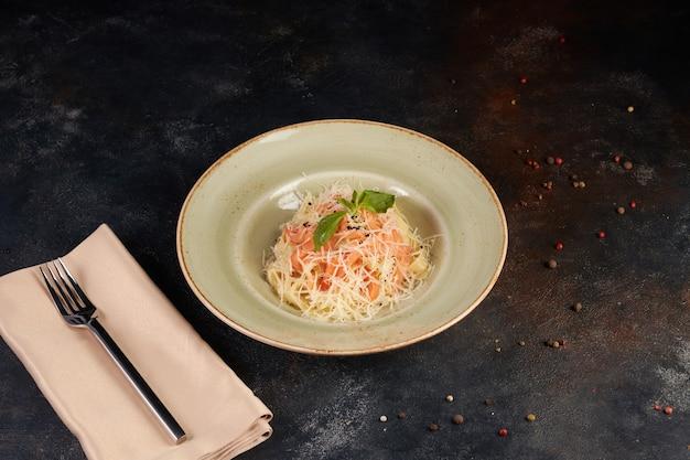 Pasta with salmon, dark background