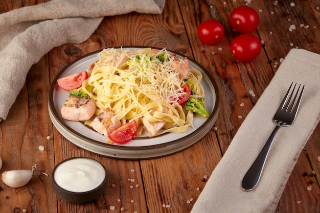 Pasta with salmon and vegetables, italian cuisine, wooden background
