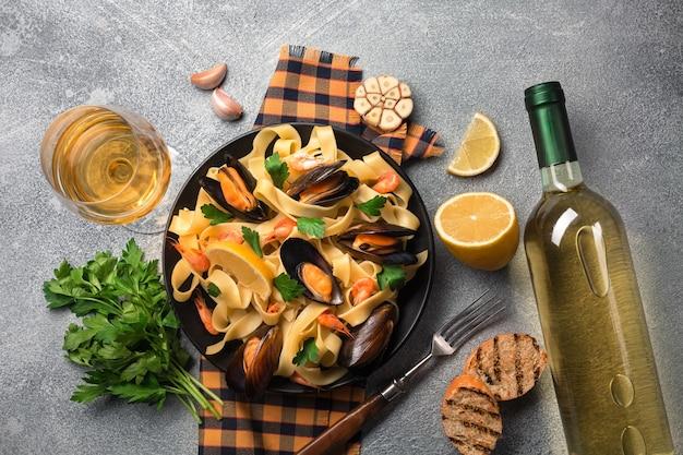 石のテーブルにシーフードと白ワインのパスタ。ムール貝とエビ。上面図。