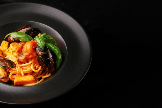 어두운 테이블에 검은 접시와 해산물 근접 촬영 파스타. 홍합, 새우, 토마토를 곁들인 이탈리아 스파게티 파스타 마리 나라