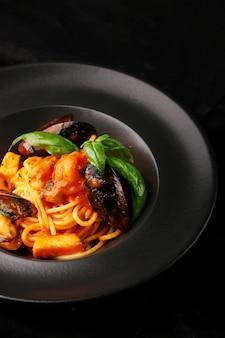 어두운 테이블에 검은 접시와 해산물 근접 촬영 파스타. 홍합, 새우, 토마토를 곁들인 이탈리아 스파게티 파스타