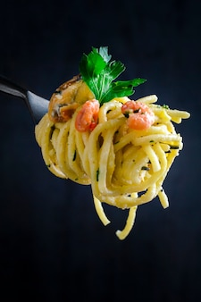 Pasta with seafood in a creamy sauce on a fork on a dark background. close-up.