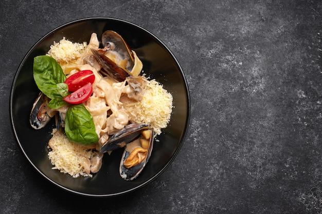 Паста с морепродуктами, мидиями, гребешком, рапаной и сыром, на черной тарелке