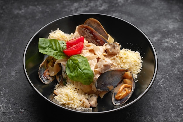 Pasta with seafood, mussels, scallop, rapana and cheese, on a black plate