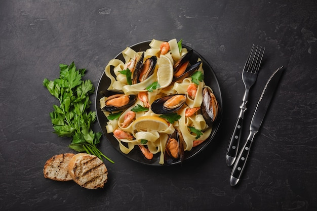 Pasta with seafood on stone table. mussels and prawns. top view with copy space.