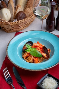 Pasta with seafood and tomato on a light background