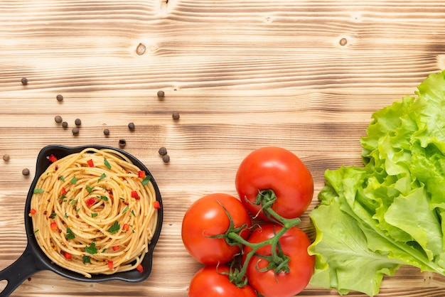 Pasta with seasonings on a wooden background. top view. copy space.
