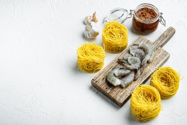 Паста с креветками, помидорами и ингредиентами соуса песто, на белой каменной поверхности, с местом для текста
