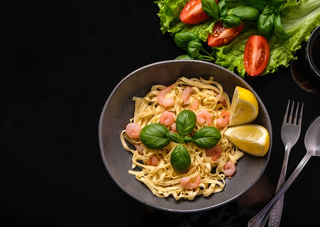 Pasta with shrimps, basil and tomatoes on a dark background. view from above