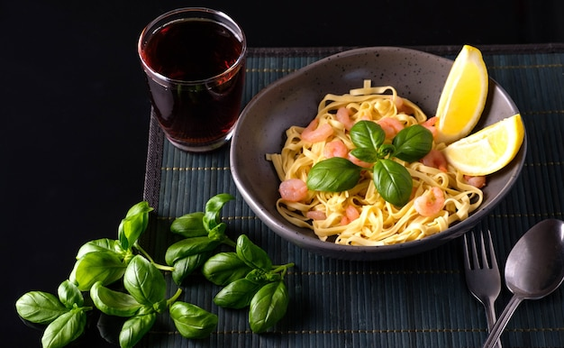 Pasta with shrimps, basil and tomatoes on a dark background