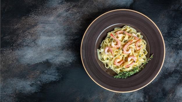 새우, 베 샤멜 소스, 타임, 페투치니 파스타를 곁들인 파스타. 해산물, 이탈리아 요리와 함께 전통적인 지중해 요리. 텍스트, 상위 뷰를위한 장소.