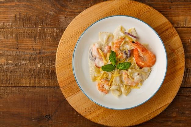 Паста с креветками в сливочном соусе, украшенная шпинатом на серой тарелке на деревянном столе на подставке.