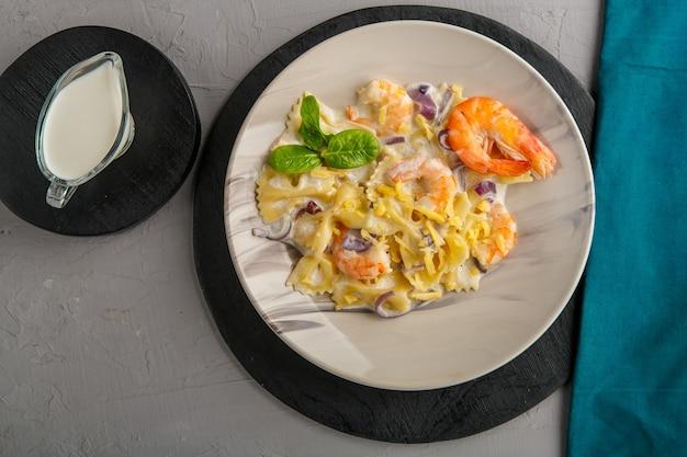 Паста с креветками в сливочном соусе на серой тарелке на бетонном фоне рядом с синей салфеткой и кувшином сливок.
