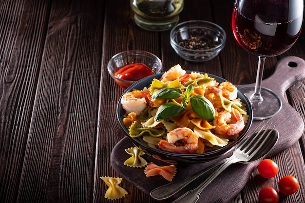 Pasta with shrimps, tomatoes, basil and spices on a wooden background