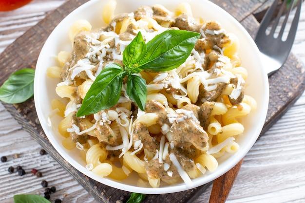 Паста со шпинатом и сырным соусом на светлом деревянном фоне.