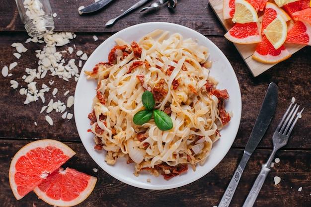 Паста с вялеными помидорами на столе, ресторанное блюдо на деревянном фоне, вид сверху