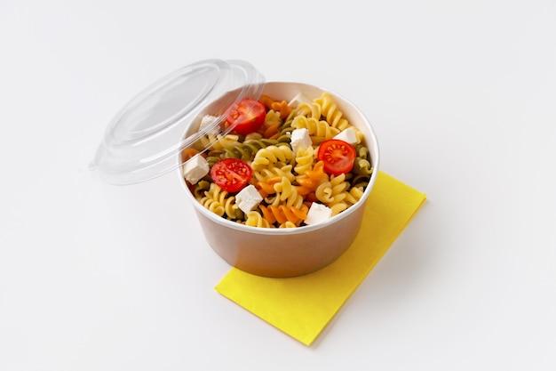 Паста с помидорами и сыром фета в коробке на белом столе