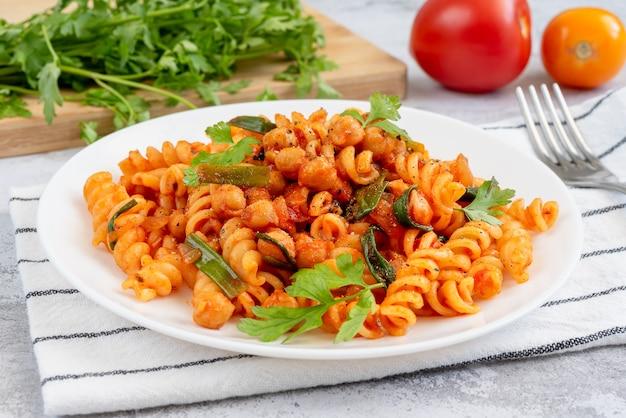 하얀 접시에 토마토 소스, 병아리콩, 파를 넣은 파스타