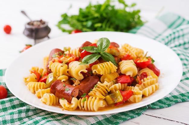 Макароны с томатным соусом с колбасой, помидорами, зеленым базиликом оформлены в белом фоне на деревянном столе.