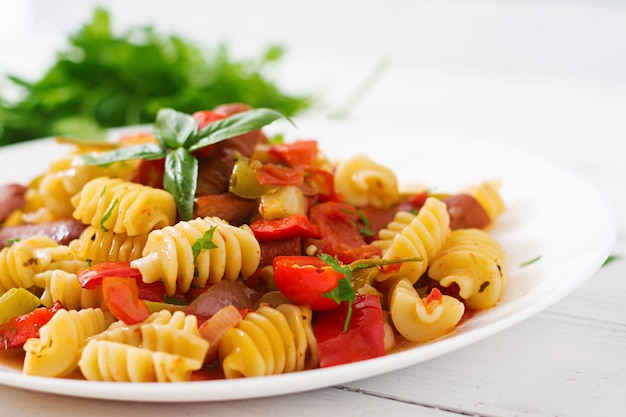 Pasta with tomato sauce with sausage, tomatoes, green basil decorated in white plate on a wooden table.