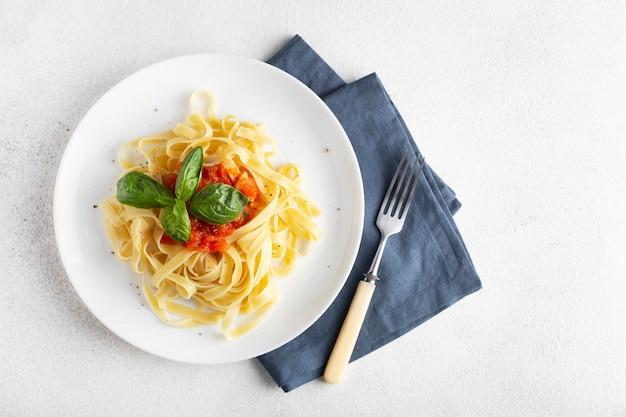 Паста с помидорами и базиликом в белой тарелке