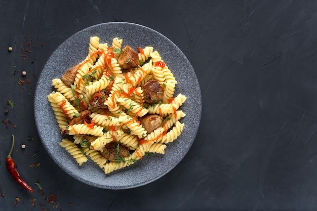 暗いテーブルの皿にトマト、チキン、パセリのパスタ。プレミアム写真。