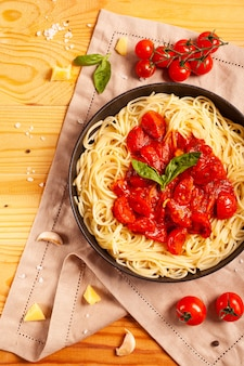 Pasta with tomatoes in a pan on a wooden background