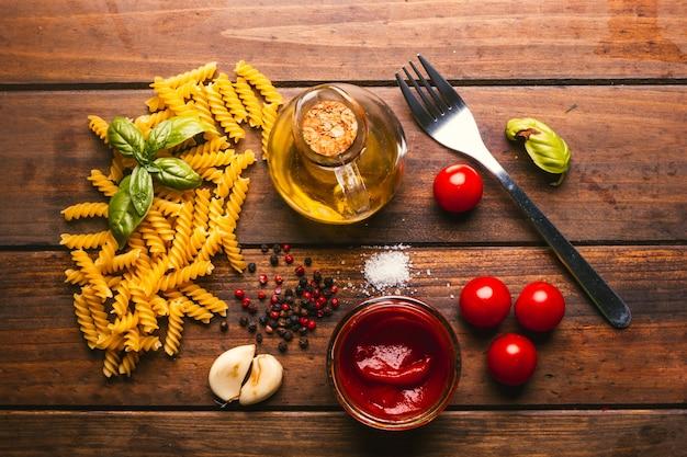 Паста с различными ингредиентами для приготовления итальянской еды на деревенском деревянном столе